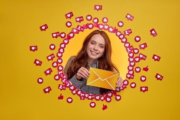 Femme rousse tenant un message de lettre, isolé sur un mur jaune