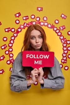 Femme rousse tenant une pancarte suivez-moi, demandez à être plus active sur internet