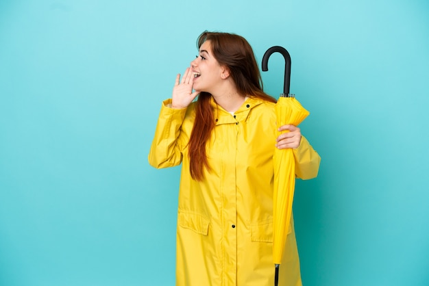 Femme rousse tenant un parapluie isolé sur fond bleu criant avec la bouche grande ouverte sur le côté