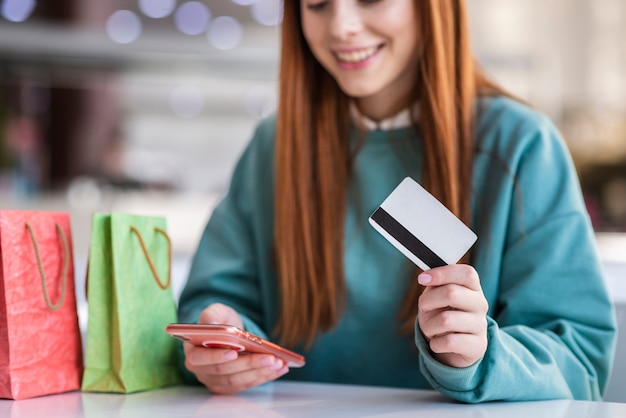 Femme rousse tenant un téléphone et une carte de crédit