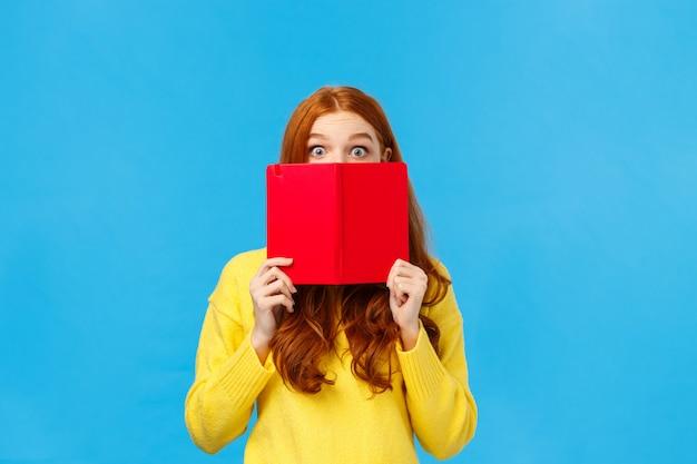 Femme rousse timide et mignonne comme lire des livres et écrire dans un journal, se cachant le visage derrière un cahier cool rouge
