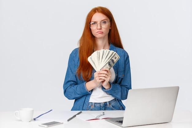 Femme rousse avec ventilateur de billets de banque