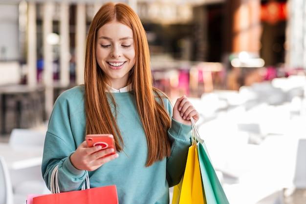 Femme rousse vérifiant son téléphone