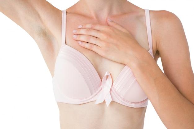 Femme avec un ruban rose sur son soutien-gorge pour la sensibilisation au cancer du sein
