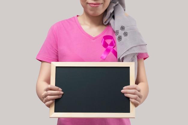 Femme avec ruban rose tenant un tableau noir.