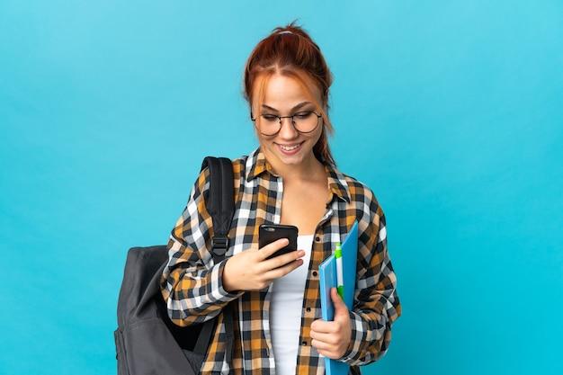 Femme russe étudiante isolée sur bleu envoyant un message avec le mobile