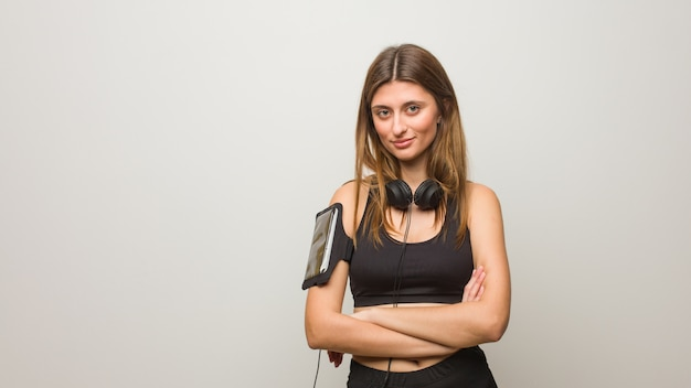 Femme russe de fitness jeune traversant les bras, souriant et détendu