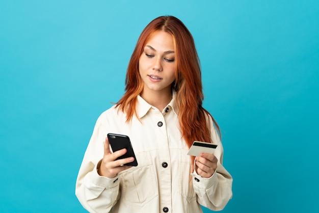 Femme russe isolée sur bleu achat avec le mobile avec une carte de crédit