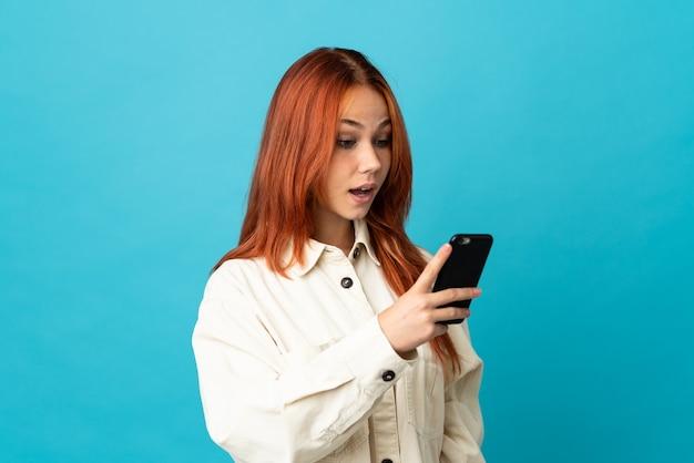 Femme russe isolée sur bleu envoyer un message ou un e-mail avec le mobile