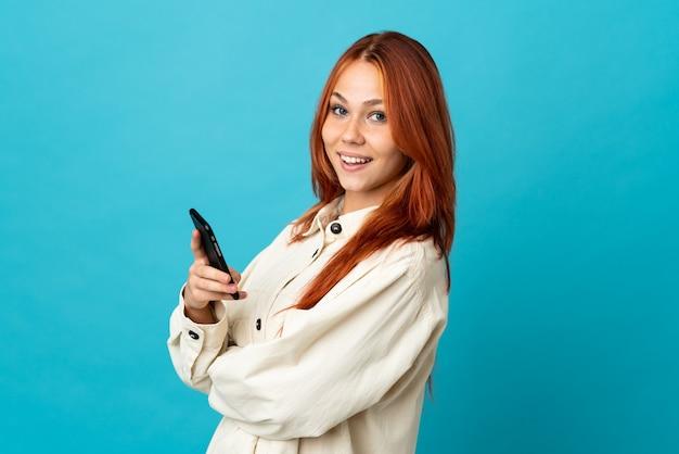 Femme russe isolée sur bleu tenant un téléphone mobile et les bras croisés