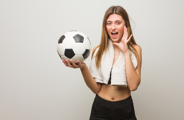 Femme russe jeune fitness criant quelque chose de heureux à l'avant. tenir un ballon de foot.