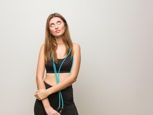 Femme russe jeune fitness fatigué et ennuyé. tenant une corde à sauter.
