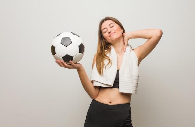 Femme russe jeune fitness souffrant de douleurs au cou. tenir un ballon de foot.