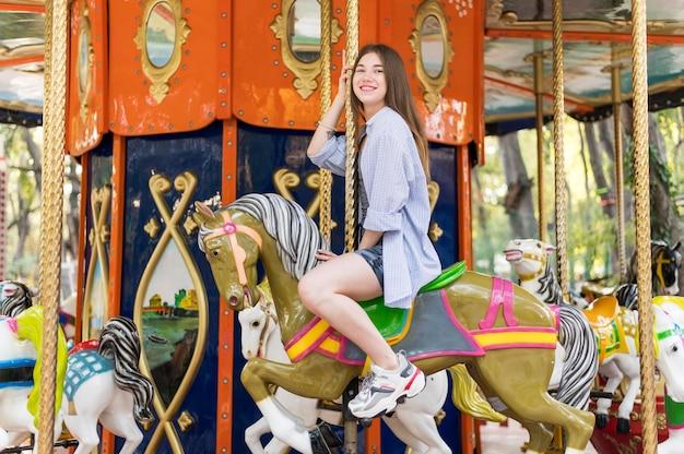 Femme s'amusant sur le carrousel