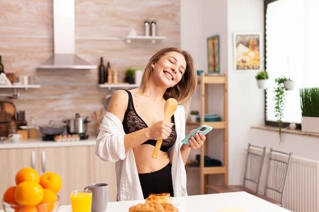 Femme s'amusant à chanter dans la cuisine pendant le petit déjeuner tenant le téléphone en lingerie sexy. femme séduisante avec des tatouages utilisant un smartphone portant des sous-vêtements temporaires le matin.