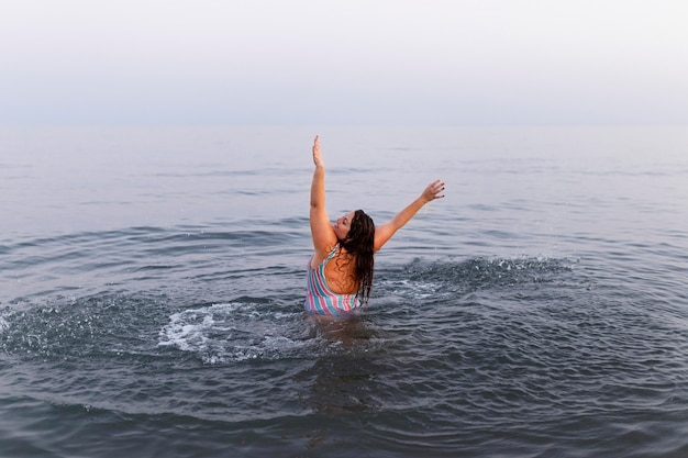 Femme s'amusant dans l'eau à la plage