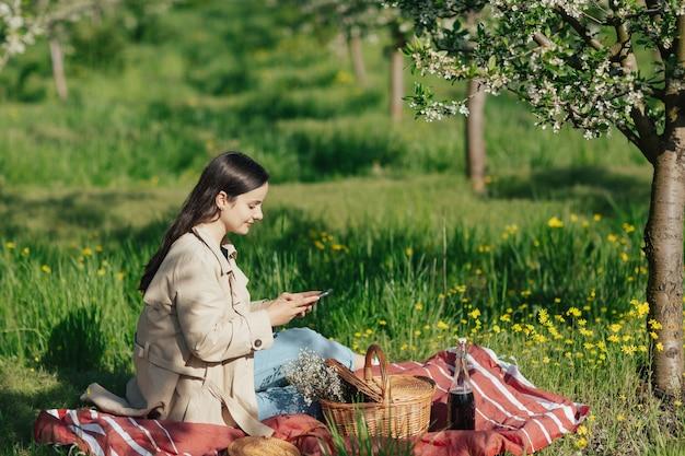 Femme s'amusant lors d'un pique-nique dans un verger