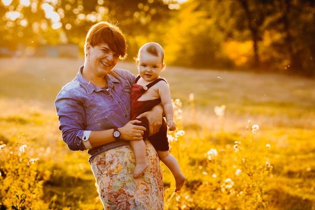 Femme s'amuse avec une petite fille debout dans les rayons du soleil d'or