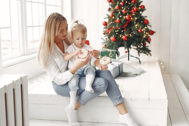 La femme s'amuse à préparer noël. mère en chemise blanche joue avec sa fille. la famille se repose dans une salle de fête.