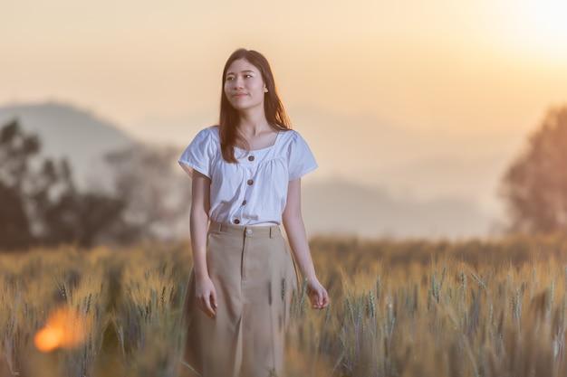 Femme s'amuser au champ d'orge au moment du coucher du soleil