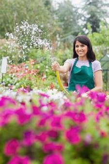Femme s'amuser tout en arrosant les plantes avec un tuyau