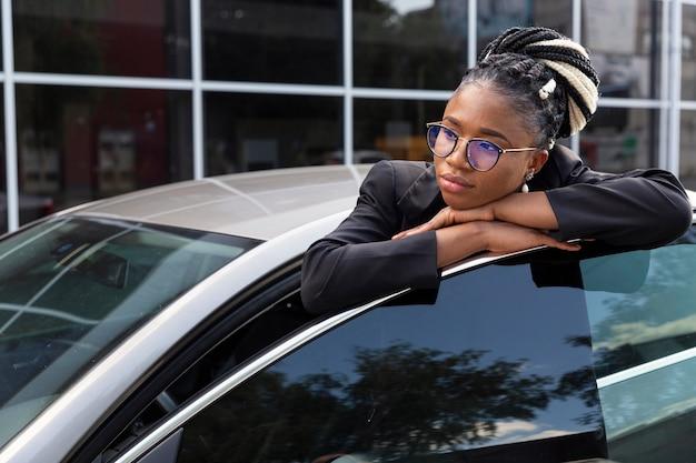 Femme s'appuyant sur la portière de sa voiture