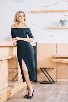 Femme s'appuyant sur une table en bois