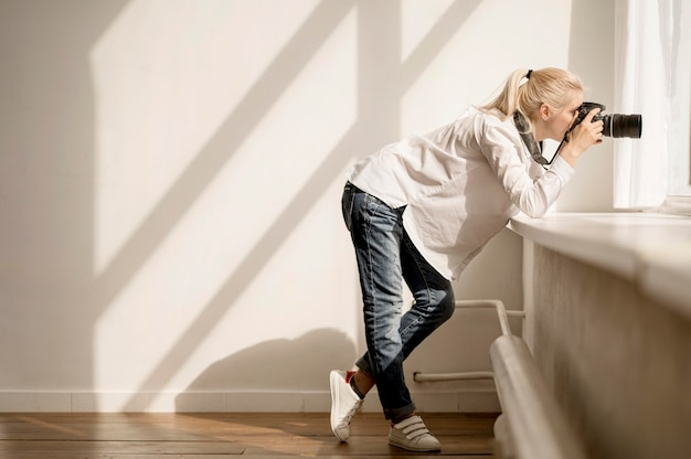 Femme, s'appuyer, rebord fenêtre, et, prendre photo