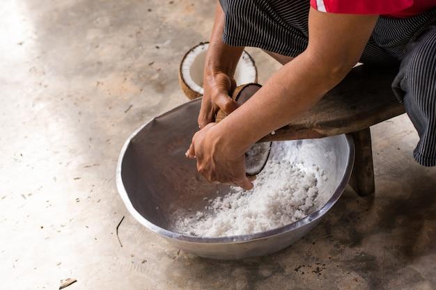 Femme s'asseoir sur une râpe à la noix de coco et râper de la noix de coco dans un bol