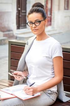 La femme s'assied sur le banc avec le smartphone et le bloc-notes