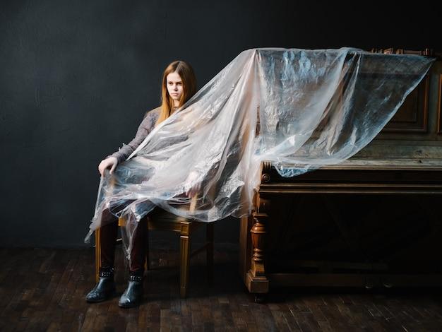 Une femme s'assied sur une chaise à côté du fond foncé de polyéthylène de piano