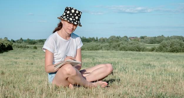 La femme s'assied sur l'herbe un jour ensoleillé et écrit dans un cahier