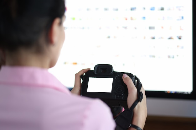 La femme s'assied à l'ordinateur et tient l'appareil-photo fonctionnant comme concept de photographe à distance