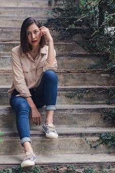 La femme s'assit avec plaisir devant le vieil escalier.