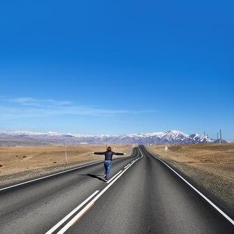 Une femme s'enfuit sur une route vide sur la vue sur la campagne le long de la région de chuysky république de l'altaï en russie