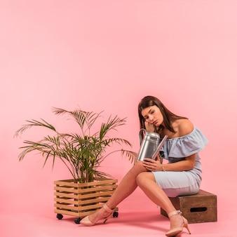 Femme s'ennuie assis avec arrosoir près de la plante