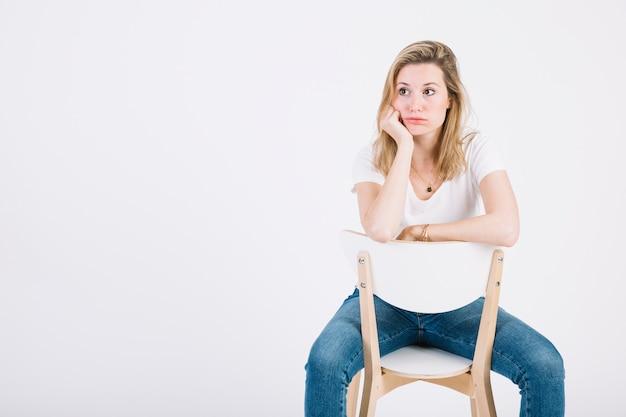 Femme s'ennuie sur une chaise