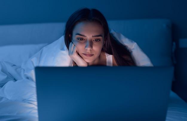 Femme s'ennuie à regarder un film sur le lit la nuit