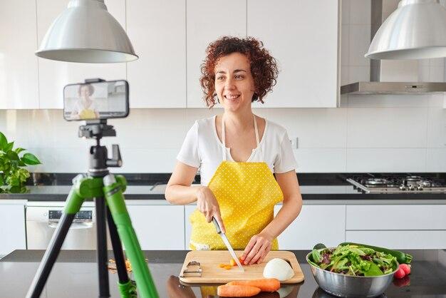 Une femme s'enregistre avec son smartphone dans sa cuisine en préparant une recette de salade