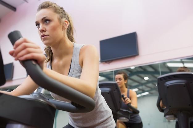 Femme s'entraînant sur un vélo d'exercice dans un cours de spinning