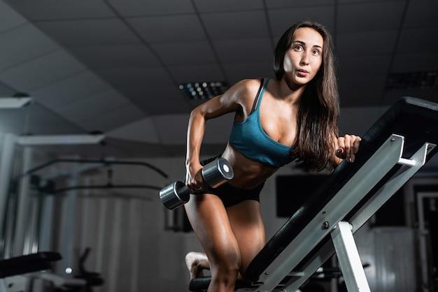 Femme s'entraîne dans la salle de sport