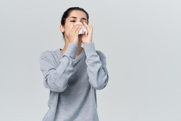 La femme s'essuie le nez avec un nez qui coule d'allergie d'infection de mouchoir