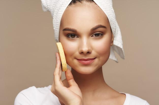 Une femme s'essuie le visage avec une éponge douce et une serviette sur la tête, fond beige. photo de haute qualité
