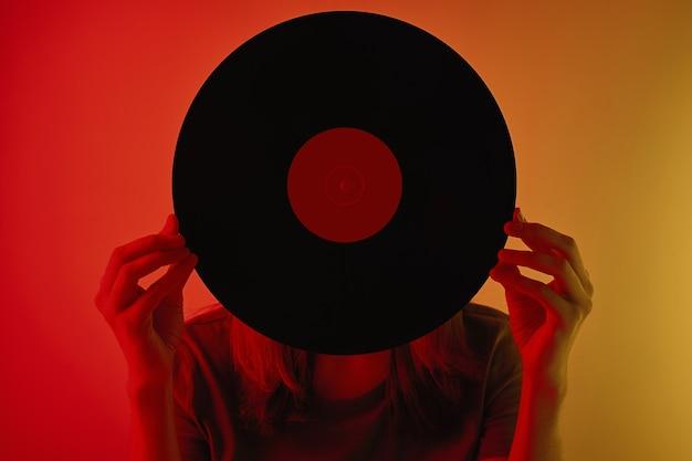 Une femme s'est couverte le visage d'un disque vinyle rétro photo tonique