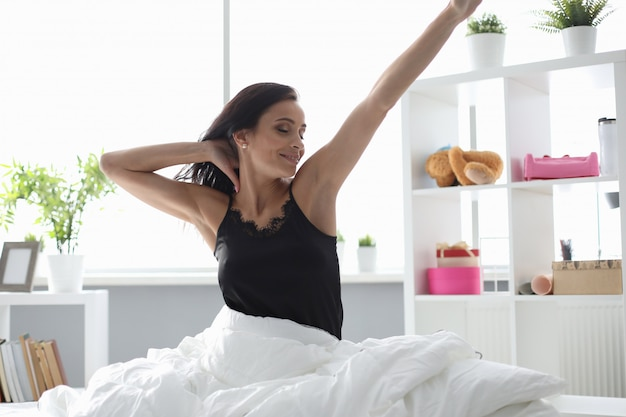 Femme s'est réveillée le matin et s'étend en souriant