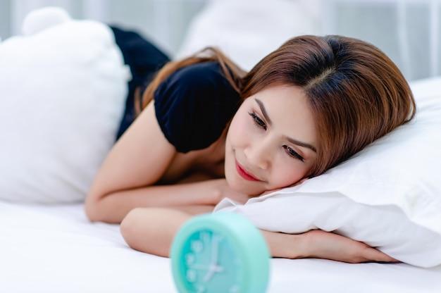 La femme s'est réveillée le matin avec un sourire éclatant. et un réveil placé sur le lit