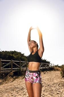 Femme s'étendant avant de courir sur le sable