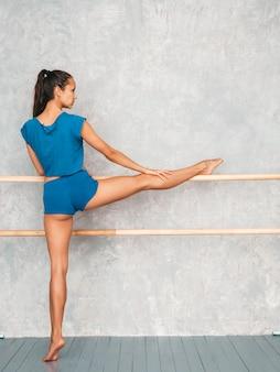 Femme s'étendant avant la formation près du mur gris en studio