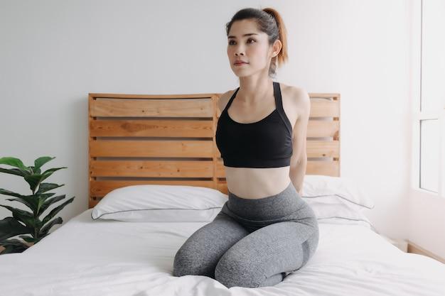 Femme s'étirant et se refroidissant après l'entraînement dans sa chambre d'appartement