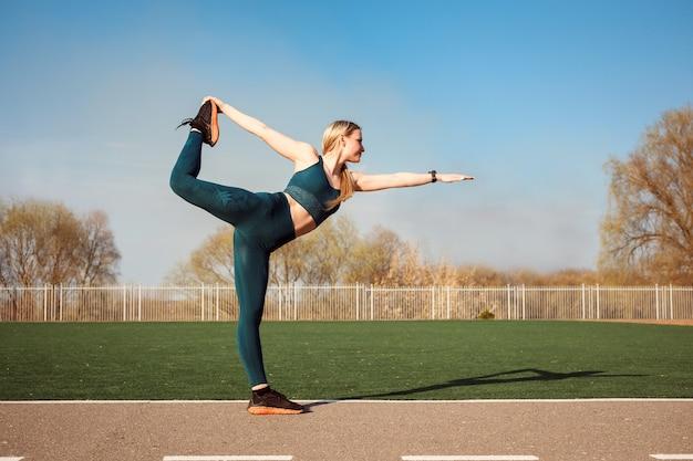 Une femme s'étire le dos et la jambe, debout dans la pose du seigneur de la danse à l'extérieur du stade